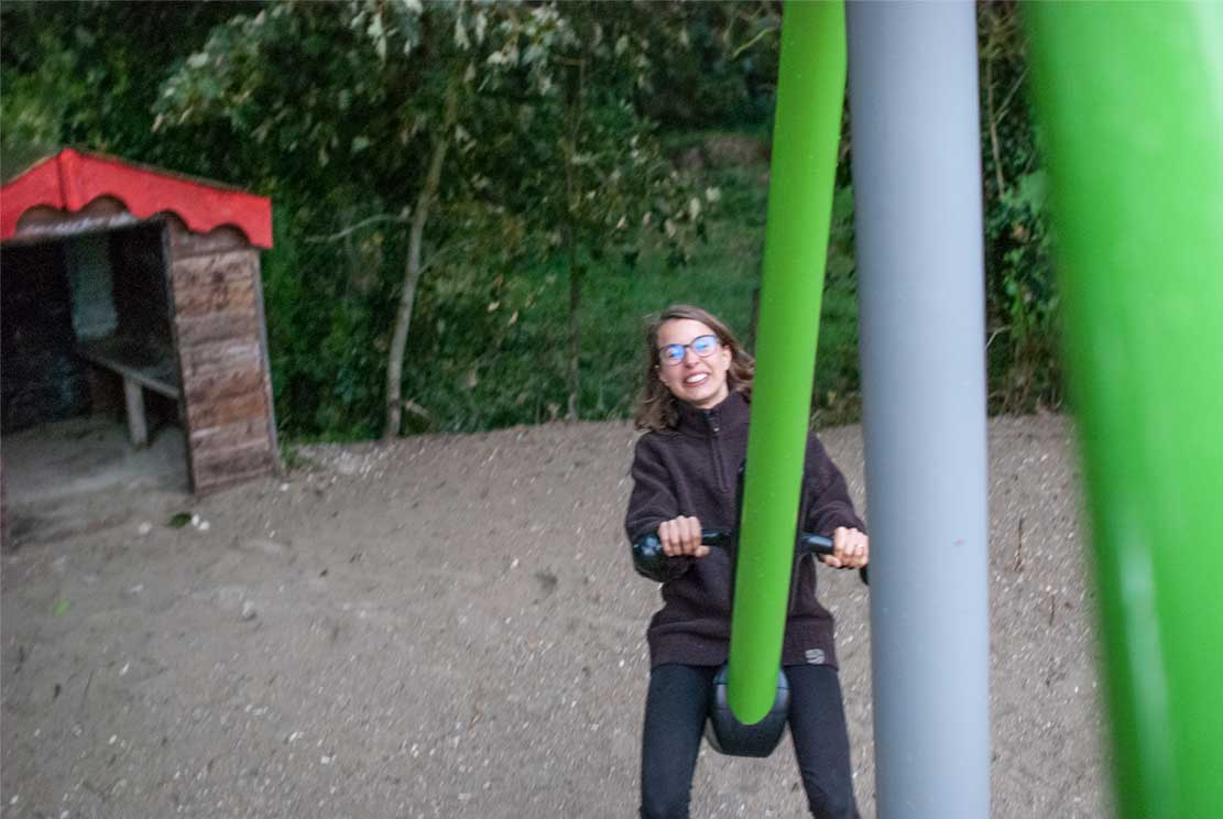 Meline laughing on a huge seesaw while me taking photo from the other side