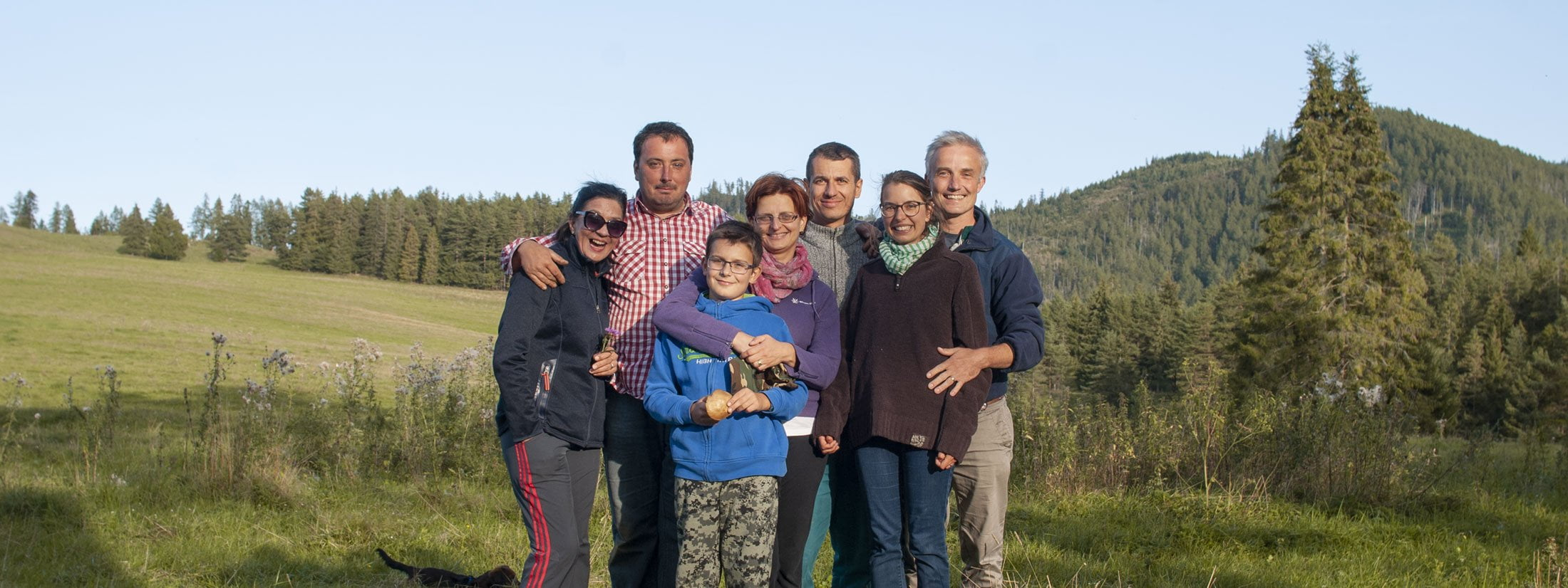 group of seven adult friends including a boy photographed on a meadow in pine woods